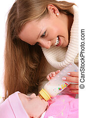 mother feeding child with bottle of milk