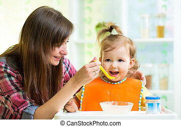 Mother feeding child with spoon indoors