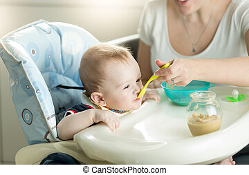 Mother feeding her 9 months old baby son sitting in child chair on kitchen