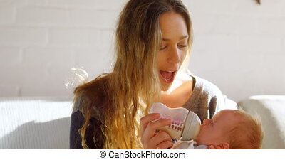 Mother feeding her baby at home 4k