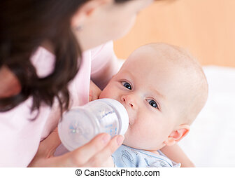 Mother feeding her baby boy with bottle