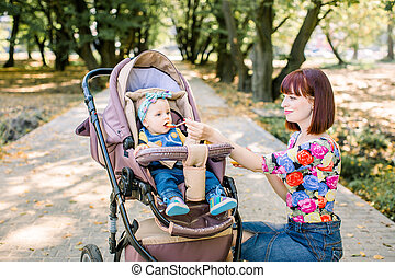 Mother Feeding Her Baby Girl with a Spoon. Mother Giving Food to her adorable Child . cute baby sitting on baby stroller carriage and posing smiling
