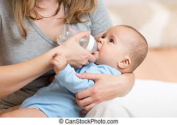 mother feeding her baby infant from bottle