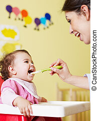 mother feeding her baby - mom giving homogenized food to her...