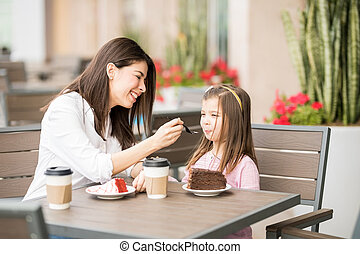 Mother feeding her daughter with cake at the cafe