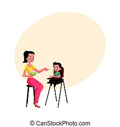 Mother feeding her son sitting in baby high chair