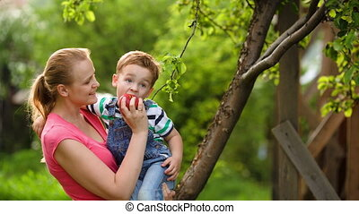 Mother feeding her son with an apple in the garden