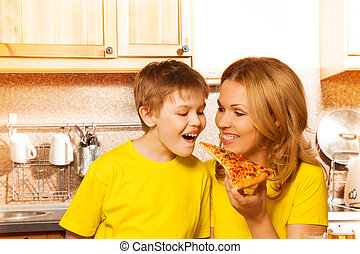 Mother feeding her son with piece of pizza