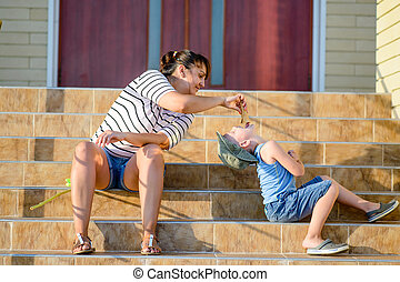 Mother Feeding Ice Cream to Son on Steps of Home