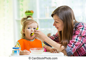 Mother feeding kid daughter at kitchen