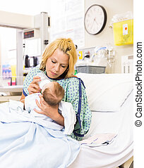 Mother Feeding Milk To Baby Girl In Hospital Bed