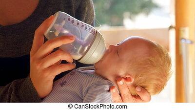 Mother feeding milk to her baby boy in living room 4k