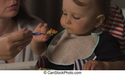 Mother feeding porridge to her baby child boy indoor children room - Young mom in gray home wear and her son eating sitting in baby seat - Happy smiling people