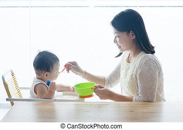 Mother feeding toddler.