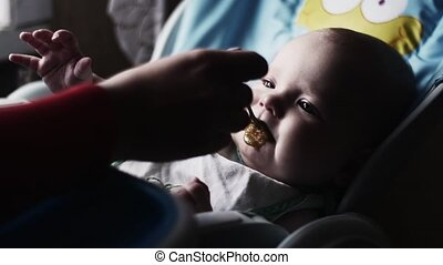Mother feeding with spoon adorable baby at children table by puree. Motherhood.