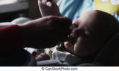Mother feeding with spoon cute baby at children table by puree. Motherhood.
