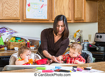 A mother in the kitchen feeds babies breakfast