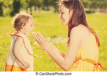 Mother feeds baby outdoors in the grass