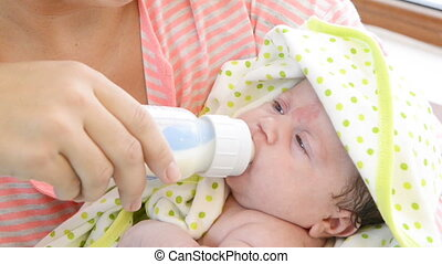 Mother feeds baby with bottle