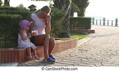 mother feeds daughter fruits out of lunch box in park