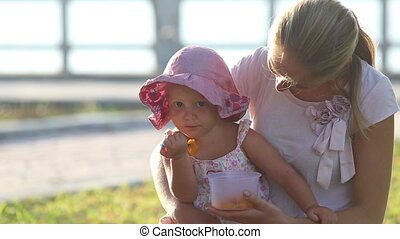 mother feeds daughter fruits out of lunch box on grass