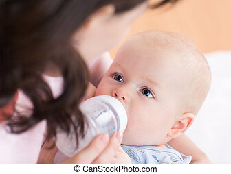 Mother feeds her baby from bottle