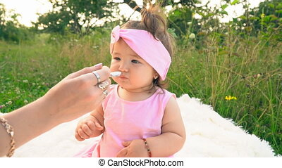 mother feeds her little daughter with yogurt - mother feeds...