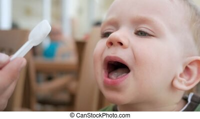 Mother feeds her young son with ice cream from a spoon. They...