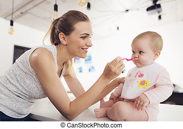 Mother feeds the baby with a spoon. The child sits on the...