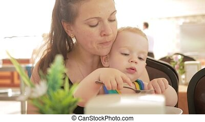 Mother feeds the cute baby boy with a spoonful of cafe. Blonde boy in a green t-shirt