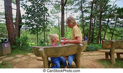 Mother Feeds with Spoon Little Girl on Wooden Bench in Park
