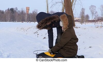 Mother fixing child winter cloth in cold morning