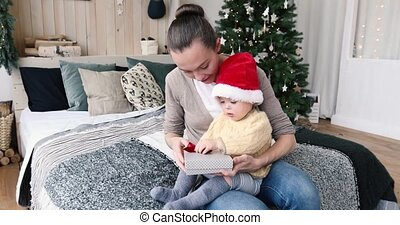 Mother gives a gift to a child for Christmas