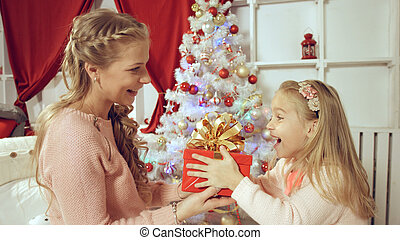 Mother gives a New Year gift to her daughter