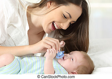 Mother giving a pacifier to her baby