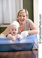 Mother giving baby a bath - Mother giving 7 month old baby a...