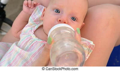 Mother giving baby daughter to drink water from the bottle