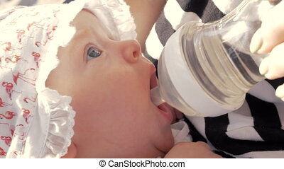 Mother giving baby girl to drink from the bottle