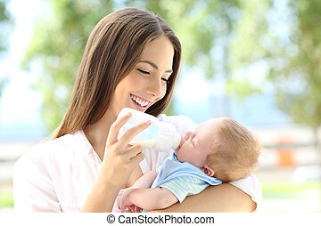 Mother giving bottle feeding to her baby