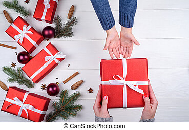 Mother giving christmas gift to son, top view. Holidays, present, childhood and happiness concept. Close up of child and mother hands with gift box on white background. Christmas family traditions