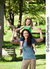 Mother giving daughter a piggyback