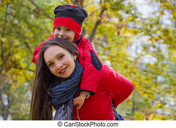Mother giving daughter piggyback ride in autumn