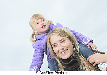 Mother giving daughter piggyback ride in autumn woodland