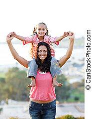 Mother giving daughter piggyback ride
