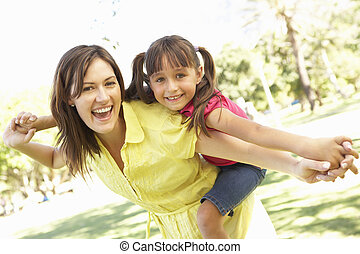 Mother Giving Daughter Ride On Back In Park