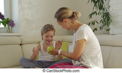 Mother giving green apple to son