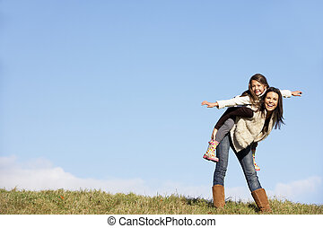 Mother Giving Her Daughter A Piggy Back Ride