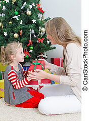 Mother giving her daughter christmas gift.