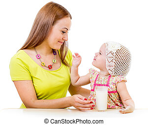 mother giving milk glass to little girl sitting at table isolated on white