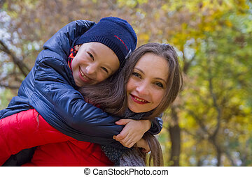 Mother giving son piggyback ride in autumn